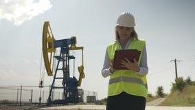 Beautiful engineering woman evaluator working on her digital tablet in oilfield industry satisfied by her job - stock video