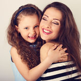 Beautiful enjoying toothy smiling mother and cute long curly sty Stock Image