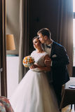 Beautiful enloved pair near bright window. Romantic moment of newlywed couple. Groom is gently holding his bride Stock Images