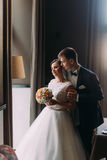 Beautiful enloved pair near bright window. Romantic moment of newlywed couple. Groom is gently holding his pretty bride Royalty Free Stock Photos