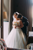 Beautiful, enloved pair near bright window in wedding hall before the celebration. Romantic moment of newlywed couple Stock Photo
