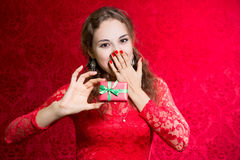 Beautiful enthusiastic girl with a small gift in a red dress Stock Photos