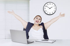 Beautiful entrepreneur lifting hands in office. Portrait of beautiful entrepreneur lifting hands while sitting in front of her laptop in the office Stock Images