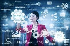 Beautiful entrepreneur using SEO button Stock Images