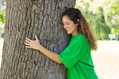Beautiful environmentalist embracing tree trunk Stock Photos