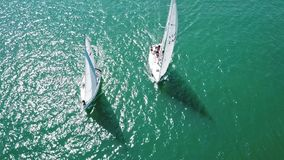 Beautiful epic drone aerial footage on warm sunny day at blue open ocean at sea, white professional yacht during racing stock footage