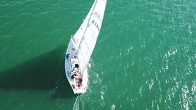 Beautiful epic drone aerial footage on warm sunny day at blue open ocean at sea, white professional yacht during racing stock video footage