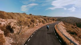 Hipster man rides on skateboard on mountain road. Beautiful and epic shot from drone of lonely figure of teenager or man skateboard down mountain road on amazing stock video footage