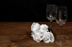 Beautiful etched wine glasses with awhite roses on wooden table and dark background. Valentines, Mothers Day, Easter, Christmas, Wedding Concepts stock images