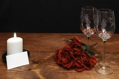Beautiful etched wine glasses with red roses and white candle on wooden table and dark background stock image