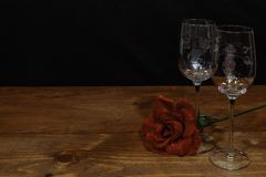 Beautiful etched wine glasses with a single red rose on wooden table and dark background stock photography