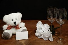 Beautiful etched wine glasses with white roses and white teddy bear and name tag on wooden table and dark background. Valentines, Mothers Day, Easter stock images