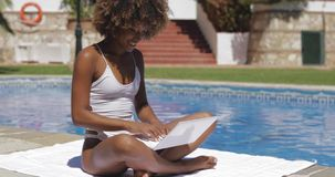 Charming girl with laptop in pool stock video footage