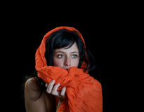 Beautiful ethnic woman. Beautiful ethnic woman behind an orange scarf surrounded by a black background Stock Photos