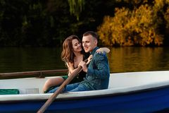 Young european couple is boating on a lake, young man and his girlfriend are sitting into boat at sunset, couple in love. Beautiful european couple is boating on royalty free stock photo