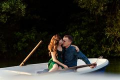 Young european couple is boating on a lake, young man and his girlfriend are sitting into boat at sunset, couple in love. Beautiful european couple is boating on stock photo