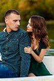 Young european couple is boating on a lake, young man and his girlfriend are sitting into boat at sunset, couple in love. Beautiful european couple is boating on royalty free stock images