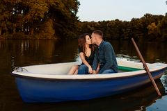 Young european couple is boating on a lake, young man and his girlfriend are sitting into boat at sunset, couple in love. Beautiful european couple is boating on royalty free stock photos