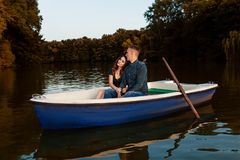 Young european couple is boating on a lake, young man and his girlfriend are sitting into boat at sunset, couple in love. Beautiful european couple is boating on stock images