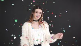 Beautiful European girl throwing up color confetti and looks at the camera, , gray background, slow motion. Beautiful European girl throwing up color confetti stock video