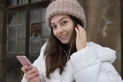Beautiful European girl in a white jacket and knitted hat listening to music with headphones walking around the city on stock images