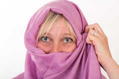 Beautiful european mid aged woman hiding her face behind a shawl Royalty Free Stock Image