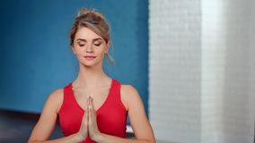 Beautiful european smiling woman meditating with closed eyes relaxing at class studio. Medium close-up. Adorable fitness girl practicing yoga showing namaste stock video footage