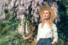 Girl in straw hat and wisteria royalty free stock photography