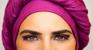 Beautiful European woman in a bright pink turban and beautiful makeup . The style of urban fashion. Portrait close up Royalty Free Stock Photography