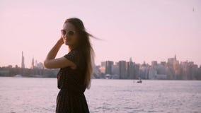 Beautiful European woman in sunglasses looks back at camera smiling, enjoying summer sunset, slow motion medium shot. Cheerful girl posing, looking at amazing stock video footage