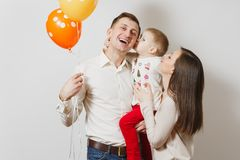 Beautiful European young people on a white background. Emotions, family concept. Joyful young man, women holding, kissing, hugging little cute child boy, air stock image