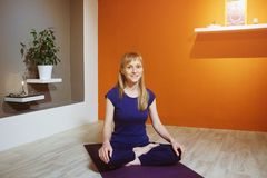 Beautiful European young woman sitting in Lotus position on purple yoga Mat, indoors, looking at camera and smiling. Time for yoga stock photography