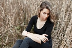 Beautiful european young woman in vintage jeans in black fashionable t-shirt sits among autumn dry grass in a field. stock photography