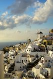 Beautiful evening light scene of Oia white building townscape along island mountain, Aegean sea, abstract cloud and blue sky royalty free stock photo