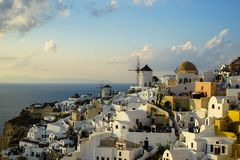 Beautiful evening light scene of Oia white building townscape and windmill along island mountain, vast Aegean sea, soft cloud royalty free stock images
