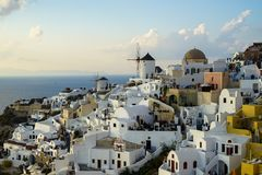 Beautiful evening light scene of Oia white building townscape and windmill along island mountain, vast ocean, soft cloud royalty free stock photo