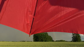 Beautiful  evening rainbow over  fields and red umbrella fragment. Beautiful  evening rainbow over farmland fields and red umbrella fragment stock video