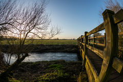 A beautiful evening by the river. With a blue sky and setting sun, by a footbridge Royalty Free Stock Photo