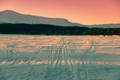 Beautiful evening sky above the lake, forest and mountain. Ski tracks on a lake with mountains and a beautiful evening sky in the background Royalty Free Stock Photography