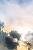 Beautiful evening skyscape. Sun`s rays shine through hole in black clouds after rain Royalty Free Stock Photography