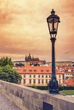 Beautiful evening sunset scenery Of the Old Town and Charles Bri. Dge over Vltava river in Prague, Czech Republic / Old Street Lamp At Sunset On Charles Bridge Royalty Free Stock Photos