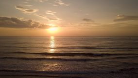 Beautiful evening sunset in sky over sea on sandy beach. Group people on motorcycle watching golden sunrise in morning
