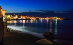 Free Beautiful Evening With Night Shore With A Beach And Umbrellas And Highlighted With Bright Colorsin Hersonissos Bay Crete Stock Photos - 104420093