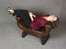 Beautiful everyday woman reclining. On leather couch Royalty Free Stock Photo