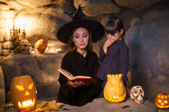 Beautiful evil witch is showing the kid witchcraft Royalty Free Stock Photo