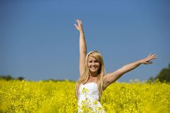 A beautiful excited girl smiling in a field of yellow flowers Stock Images