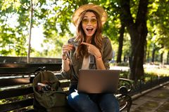 Beautiful excited happy woman outdoors sitting using laptop computer holding credit card pointing. royalty free stock photo