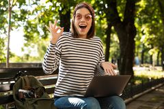 Beautiful excited happy woman outdoors sitting using laptop computer make okay gesture. stock photos