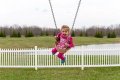 Beautiful excited little girl on a swing Royalty Free Stock Photos