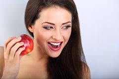 Beautiful excited makeup brunette woman holding red tasty apple Royalty Free Stock Images
